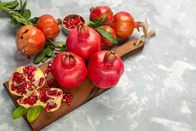Half-top view fresh red pomegranates sour and mellow fruits on light white desk fruit fresh mellow ripe tree Free Photo