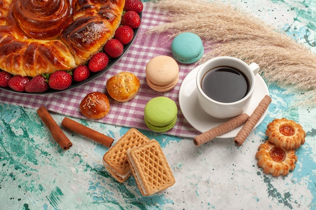 ハーフトップビューおいしい甘いパイと赤いイチゴのフレンチマカロンと水色の机の上のお茶 無料写真