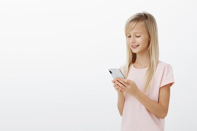Profilo girato a metà della bambina intelligente creativa con i capelli biondi in maglietta rosa, che tiene smartphone e sorride allo schermo, giocando a un gioco divertente sul dispositivo, godendo di trascorrere del tempo sul muro grigio Foto Gratuite