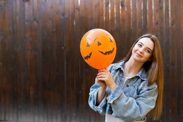 Хэллоуин осень фон с девушкой, держащей оранжевый воздушный шар Premium Фотографии
