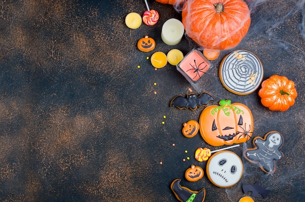 Halloween background with gingerbread, pumpkins and candles Premium Photo