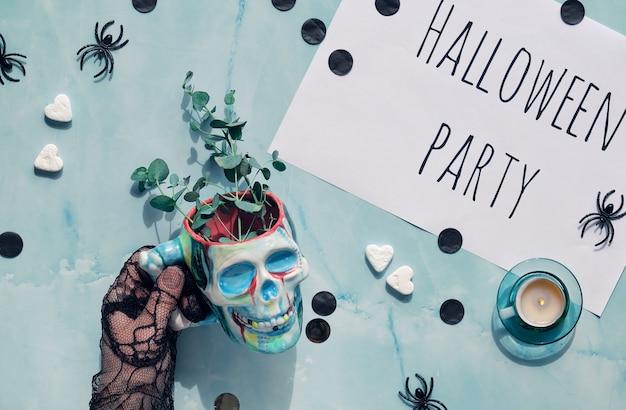 ユーカリの小枝とスカルカップを持っている手でハロウィンの背景。パーティーの装飾が施されたフラットレイアウト。 Premium写真