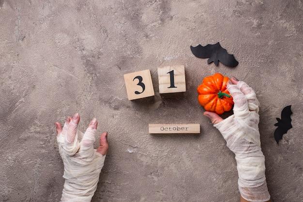 ミイラの手と木製のカレンダーとハロウィーンの背景 Premium写真