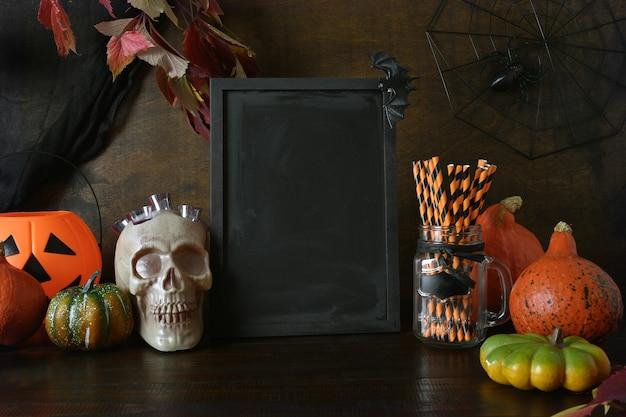 호박, 두개골, 유령 거미, 호박 머리 잭-오-랜턴 할로윈 빈 초대장. 칠판에 텍스트를위한 공간입니다. 프리미엄 사진