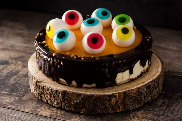 Halloween cake with candy eyes decoration on wooden table Premium Photo