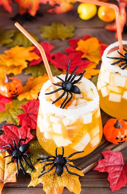 ハロウィーンのカクテル。木製のテーブルの上にグラスにリンゴと氷のかけらとフルーツジュース。 Premium写真