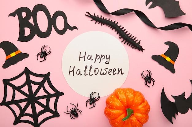 ピンクのパステルカラーの背景にクモとコウモリとハロウィーンの構成。 Premium写真