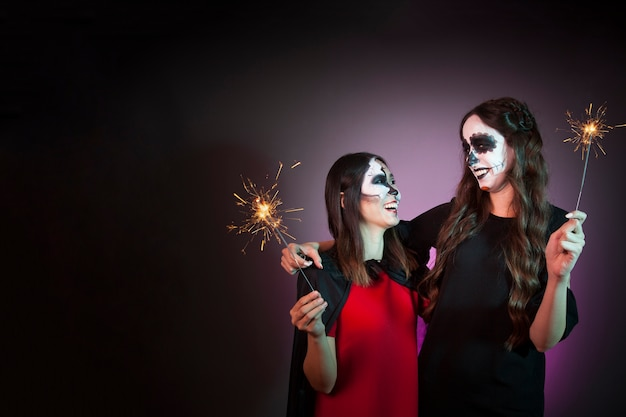 Halloween concept with women holding sparklers Free Photo