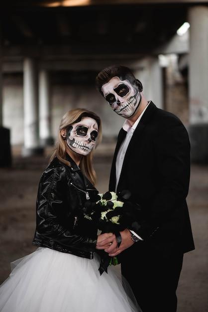 Пара хэллоуина. одетые в свадебную одежду романтическая пара зомби. Premium Фотографии