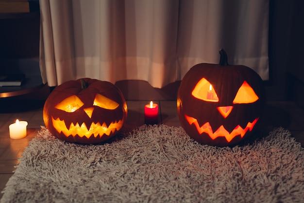 Halloween decoration. carved pumpkins with candles on kitchen. jack-o-lantern. Premium Photo