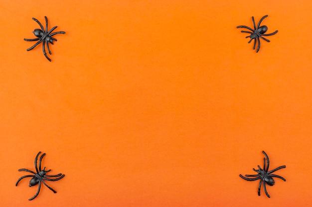 Halloween decoration: skeletons, spiders, worms on a orange background Premium Photo