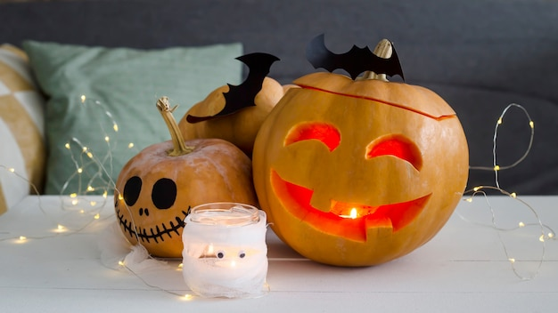 Halloween decorations - pumpkins and bats with a ghost candlestick Premium Photo