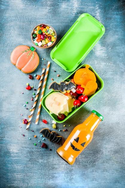 Halloween food, school lunch box with pumpkin drink bottle Premium Photo