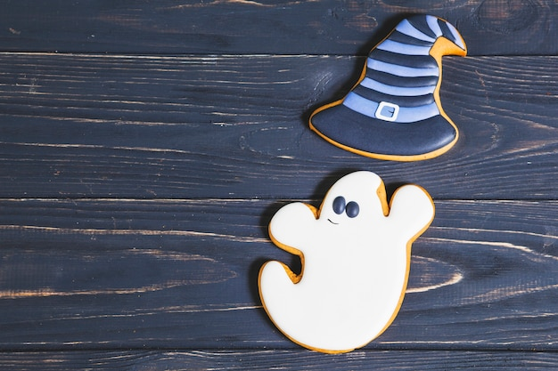 Halloweenghost with witch hat cookies on desk Free Photo