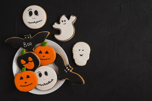 Halloween gingerbread on plate near delicious cookies Free Photo