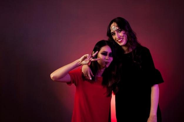 Halloween girls making peace gesture Free Photo