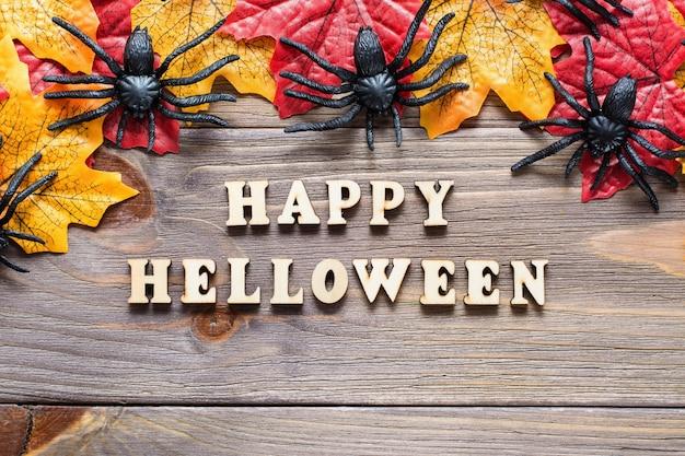 ハロウィンおめでとうございます。カエデの葉とクモに囲まれたフレーズのレタリング Premium写真