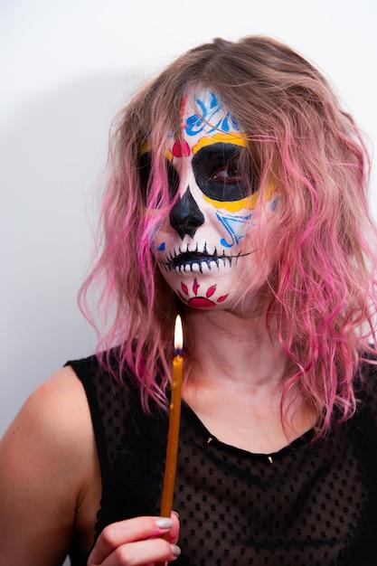 Праздник хэллоуина, портрет девушки с косметикой, держащей в руке свечу. Premium Фотографии