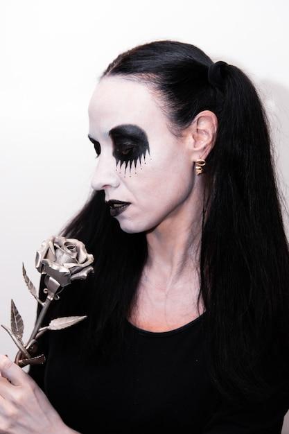 Праздник хеллоуина, портрет девушки с косметикой, держащей металлический цветок розы. Premium Фотографии