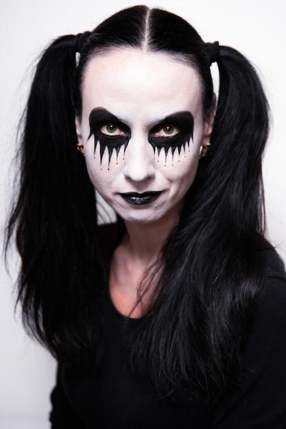 ハロウィーンの休日、化粧を持つ少女の肖像画。 Premium写真