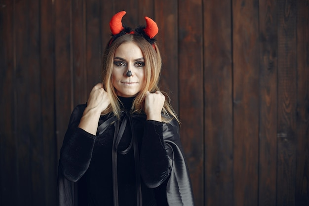 Trucco di halloween bella donna con acconciatura bionda. ragazza modello in costume nero. tema di halloween. Foto Gratuite