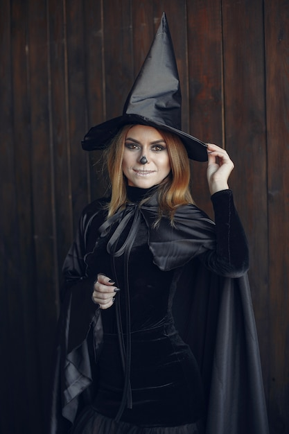 Состав хеллоуина красивая женщина с белокурой прической. модельная девушка в черном костюме. тема хэллоуина. Бесплатные Фотографии