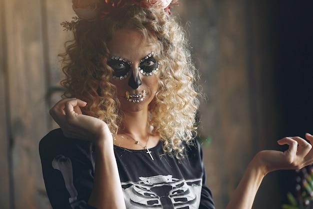 Bella donna del cranio di trucco di halloween con l'acconciatura bionda. ragazza modello santa muerte in costume nero. Foto Gratuite