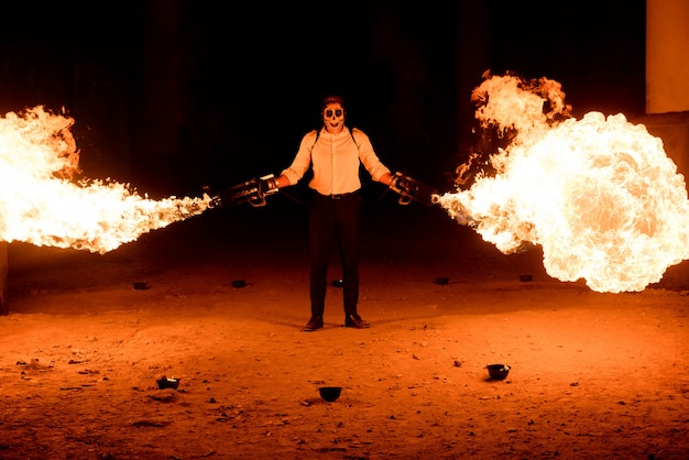 Halloween man in costume with flamethrower in his hands. devil makeup on face Premium Photo