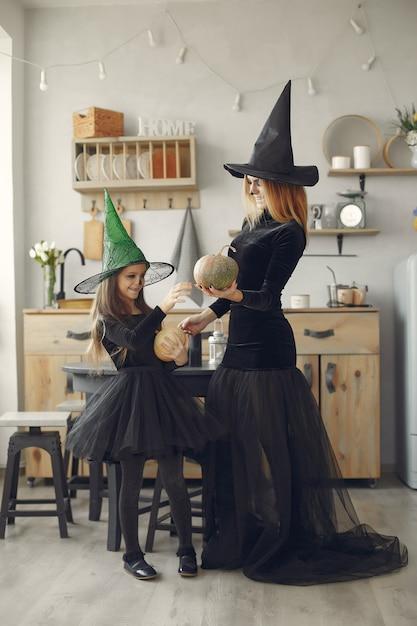 ハロウィン。ハロウィーンの衣装の母と娘。自宅で家族。 無料写真