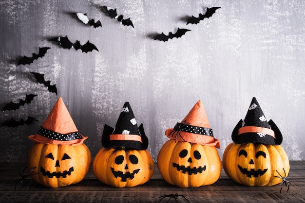 Halloween, orange ghost pumpkins with witch hat on gray wooden board Premium Photo