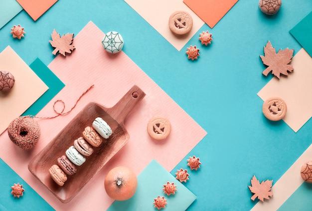 装飾されたお菓子とカエデの葉とパステルカラーのハロウィーンの紙 Premium写真