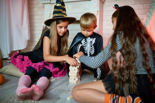 Дети играют в настольные игры на halloween party Premium Фотографии