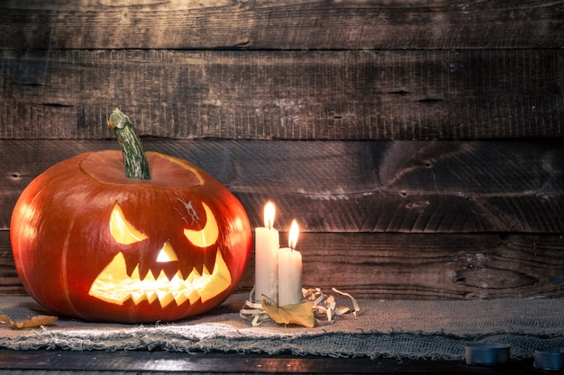 Halloween pumpkin and candles on a dark, wooden background. halloween celebration. copy space. halloween Premium Photo