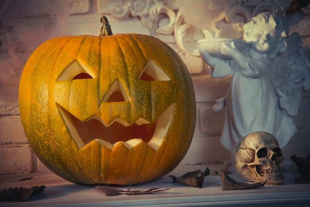 Halloween pumpkin and skull are on the table Premium Photo