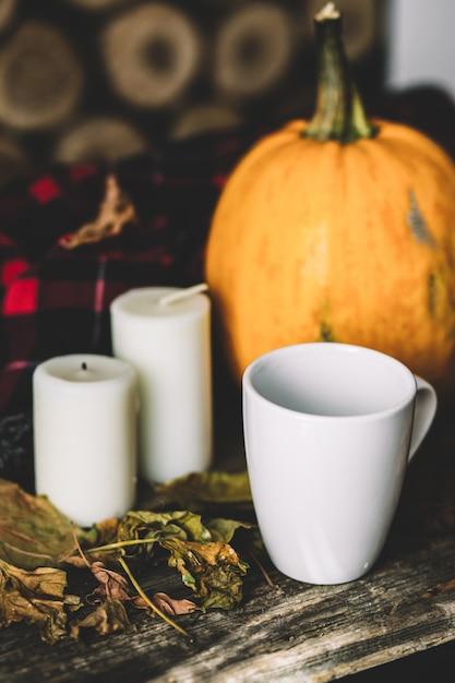 Тыква хеллоуина с кофейной чашкой на древесине. Premium Фотографии
