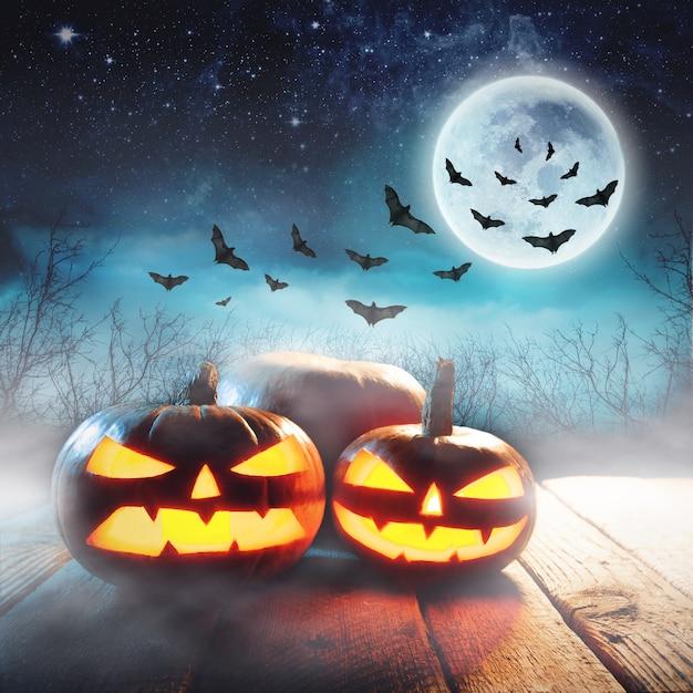 満月とコウモリと夜の神秘的な森のハロウィーンのカボチャ Premium写真