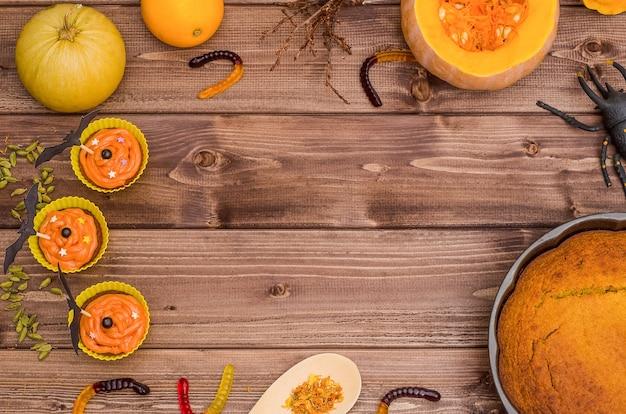 コピースペースのあるハロウィーンの表面:カボチャのパイとオレンジ色のカボチャのカップケーキ、甘いワーム、クモ Premium写真