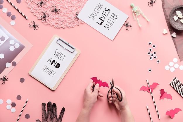 スウィートアンドスプーキーとスケルトンライフマターのテキストが入ったハロウィンテキストカードハサミで手がピンクに紙の装飾をカットしました。 Premium写真