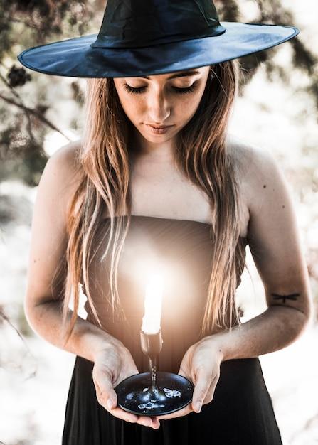 Strega di halloween guardando il candelabro nella foresta di sole Foto Gratuite