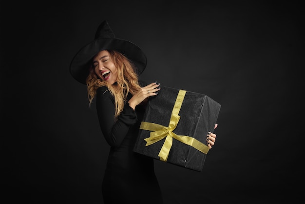 Halloween witch with a black hat on a black wall holding gift boxes Premium Photo