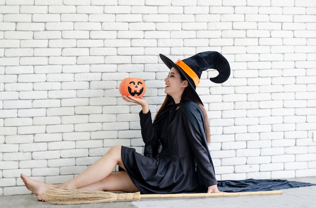 Halloween witch with a magic pumpkin ,  beautiful young woman in witches hat and costume Premium Photo