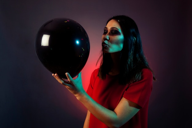 Halloween woman trying to kiss balloon Free Photo