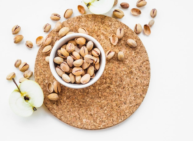 Halved apple with bowl of pistachio nuts on cork round coaster Free Photo