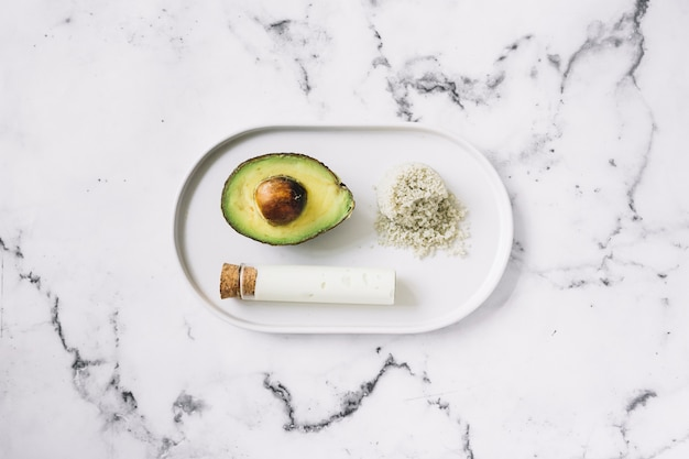 Halved avocado; grated body scrub and test tube on white tray against marble textured background Free Photo