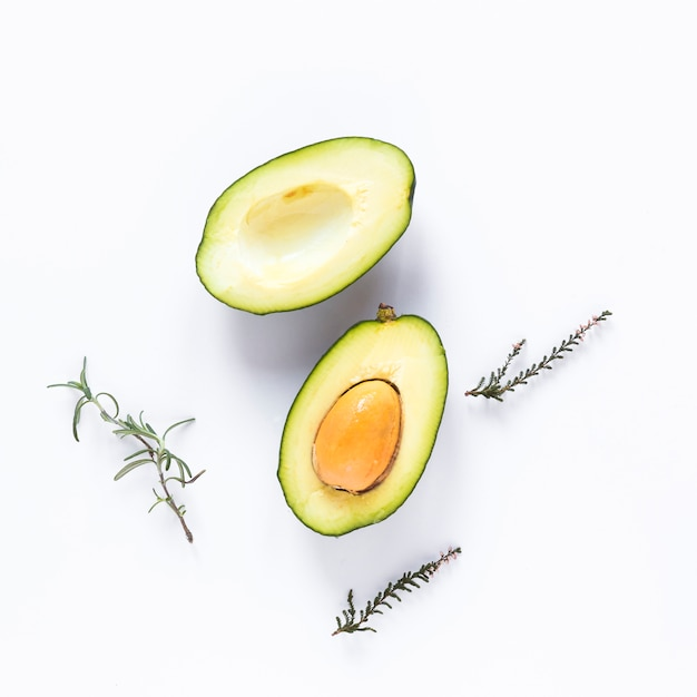 Halved avocado and herbs against white background Free Photo