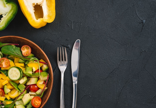 Halved bell pepper and mixed vegetable salad with cutlery on black concrete backdrop Free Photo