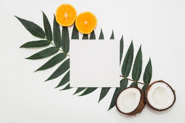 Halved coconut; juicy oranges and blank paper on green leaf against white backdrop Free Photo