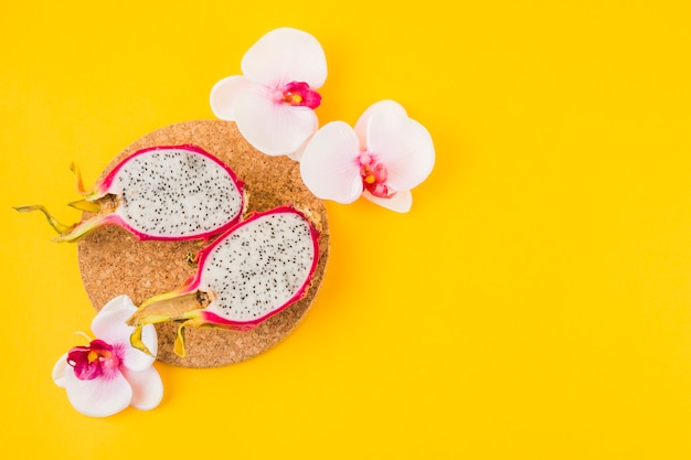 Halved dragon fruit on cork coaster with pink orchid flower on yellow backdrop Free Photo