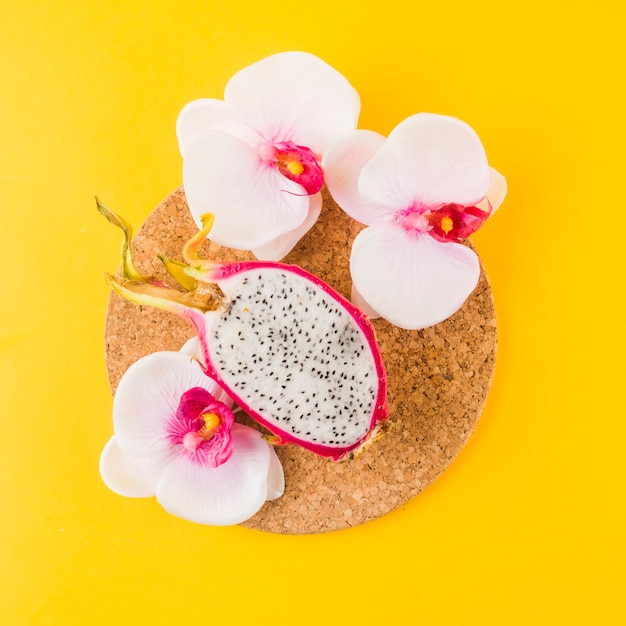 Halved dragon fruit an orchid flowers on cork coaster against yellow backdrop Free Photo