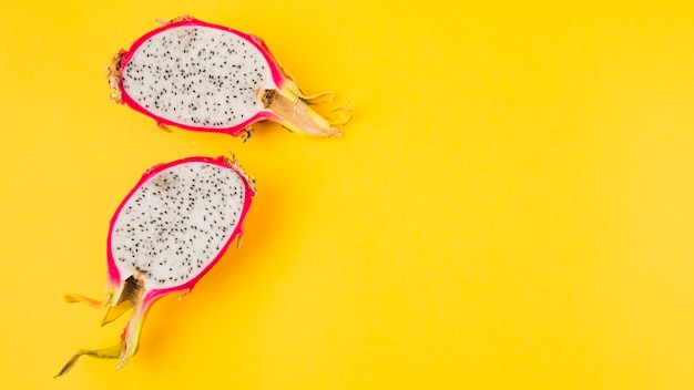 Halved dragon fruit on yellow background Free Photo